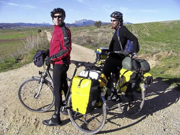 Adrian Cyr, left, and Ellery Althaus stop for a rest on their touring bikes loaded with rear panniers. Any bicycle with a rear rack can hold with panniers, also known as saddlebags. Outfitting your bicycle with a rear rack and panniers doesn't have to be expensive and helps turn your bicycle into a multi-functional mode of transportation that helps a cyclist carry their belongings on the daily commute to work or go grocery shopping.  photo by Levi Bridges
