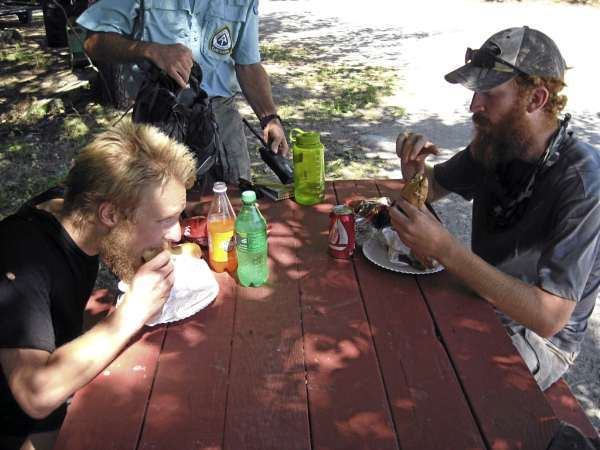Jeff &quotBoundless&quot Gants, left,  and his hiking partner Adam &quotAchilles the Red&quot Hiatt chow down on hamburgers and Italian sandwiches at the picnic table at Abol Bridge Store and campground recently. The two Appalachian Trail through-hikers took time to answer questions about their hike before entering Baxter State Park. BRAD VILES