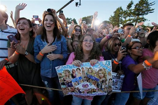 Fans react as Taylor Swift addresses the crowd at the premiere of her new video, &quotMine,&quot in Kennebunkport, Maine, Friday, Aug. 27, 2010. (AP Photo/Robert F. Bukaty)