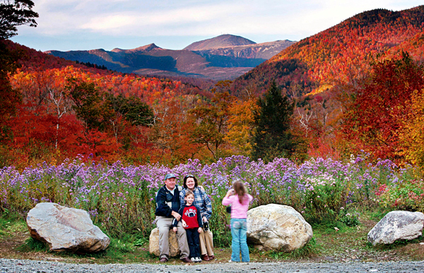 FILE - In this Oct. 6, 2006 file photo, flowers, fall foliage and 6,288-foot Mt. Washington serve as a backdrop for a family picture at Crawford Notch State Park in New Hampshire. The state of New Hampshire is exploring possible commercial sponsorship of its state parks by outdoor outfitter Eastern Mountain Sports, headquartered in New Hampshire. (AP Photo/Robert F. Bukaty, File)