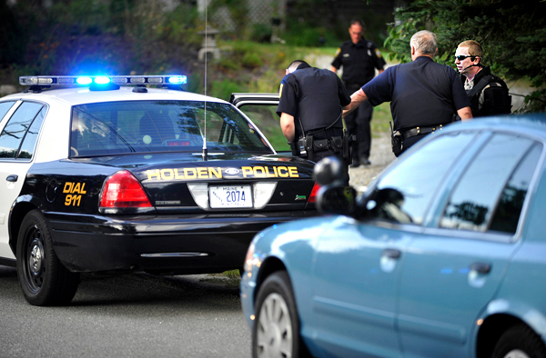 As another officer talked with the suspect in a Holden police car, Chief Troy Morton, far right, of the Penobscot County Sheriff's Dept. Special Response Team conferred with Sgt. Eugene Fizell, second from right, of the Holden Police Dept.  after officers resolved a standoff at a residence on Mann Hill Road Saturday afternoon, August 28,2010. With the help of Maine State Police, Penobscot County Special Response Team and the Maine Warden Service, a 25-year-old man was taken into custody by the Holden Police Dept. and transported to Eastern Maine Medical Center for an evaluation.  (Bangor Daily News/John Clarke Russ)