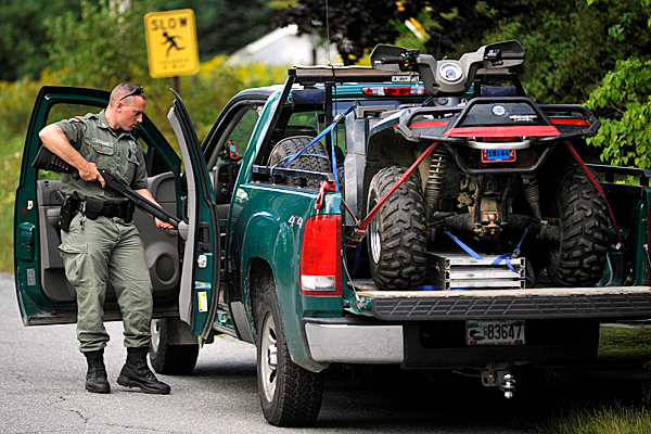 Maine Warden James Babiarz secures his firearm after officers resolved a standoff at a residence on Mann Hill Road shortly before 4 pm Saturday, August 28,2010. With the help of Maine State Police, Penobscot County Special Response Team and the Maine Warden Service, a 25-year-old man was taken into custody by the Holden Police Dept. and transported to Eastern Maine Medical Center for an evaluation.  (Bangor Daily News/John Clarke Russ)