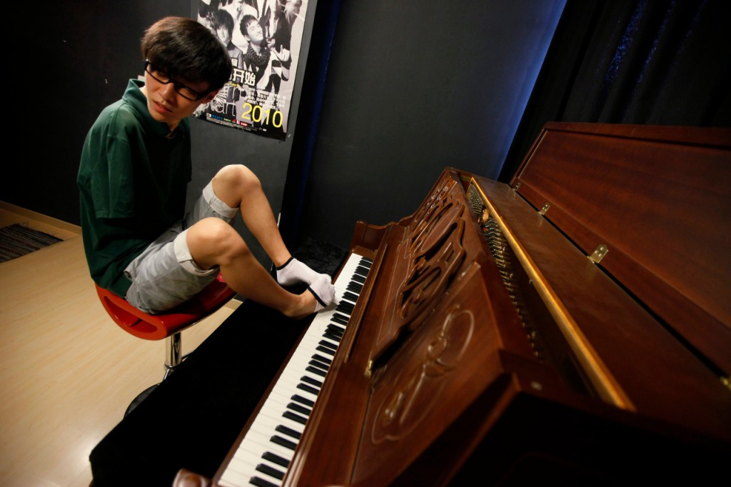 In this Aug. 26, 2010 photo, pianist Liu Wei takes off one of socks to play a piano before his practice session in Shanghai. The 23-year-old, whose arms were amputated after a childhood accident, plays the piano with his toes.  Liu was thrust into the limelight earlier this month when he performed on &quotChina's Got Talent,&quot the Chinese version of the TV show that helped make Britain's Susan Boyle a singing star. (AP Photo/Eugene Hoshiko)