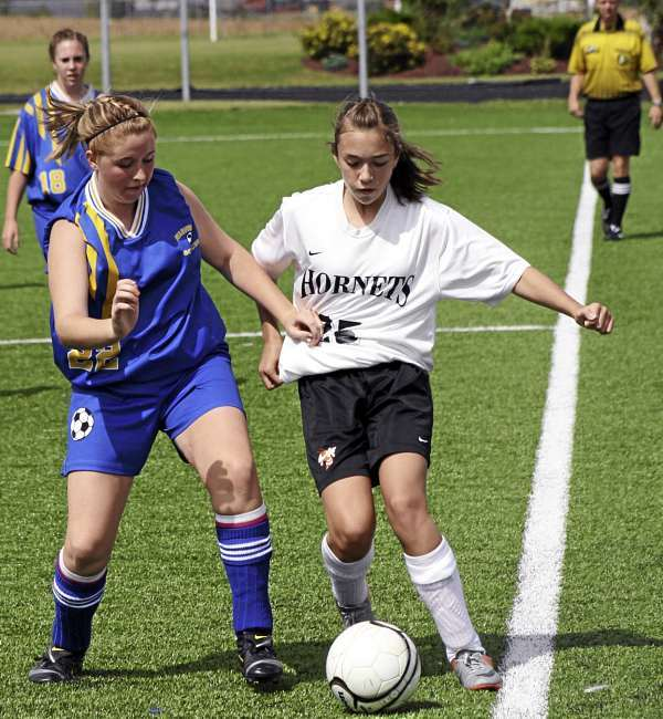 Rachel Gillis (25) of the Ashland Hornets dribbles the ball down the sideline while being defended by Washburn?s Nicole Olson during Saturday?s soccer game played in Presque Isle. Kristi Sperry of Washburn (8) and official Matt Rossignol looks in on the play. The Beavers gained a 1-0 shutout victory. (Photo by Kevin Sjoberg)