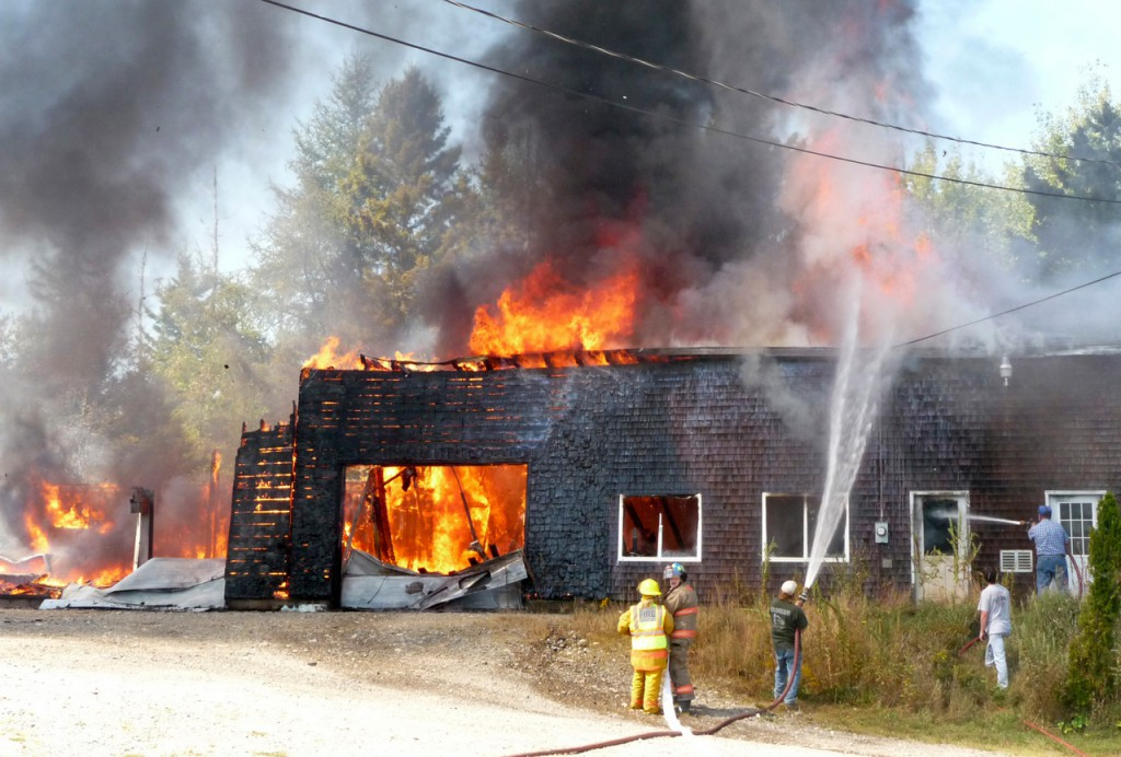 A fast moving blaze destroyed two buildings Monday afternoon on Dwelley Road in East Machias, part of a complex of buildings that housed blueberry equipment and construction tools. The building's owner, Kevin Look, said a nearby house was saved when a neighbor used a garden hose to cool off the siding while waiting for firefighters to arrive. The buildings were the former Gary's Auto Center but Look said they were now used for storage. A pickup truck, a blueberry tractor and harvester and a blueberry sprayer, as well as carpentry and construction equipment were destroyed and both buildings were a total loss. Look said family members Jeremy and Crystal Look resided in the home, which was undamaged. Firefighters from East Machias, Machias and Marshfield as well as members of the Maine Forest Service responded to the blaze. &quotI was in Machias when I saw the smoke,&quot a distraught Look said. &quotThen a friend called me and said it was my buildings. All my tools are in there. I sure don't need this.&quot Look said the electricity had been turned off to the buildings and he had no idea what caused the fire. (Bangor Daily News/Sharon Kiley Mack)