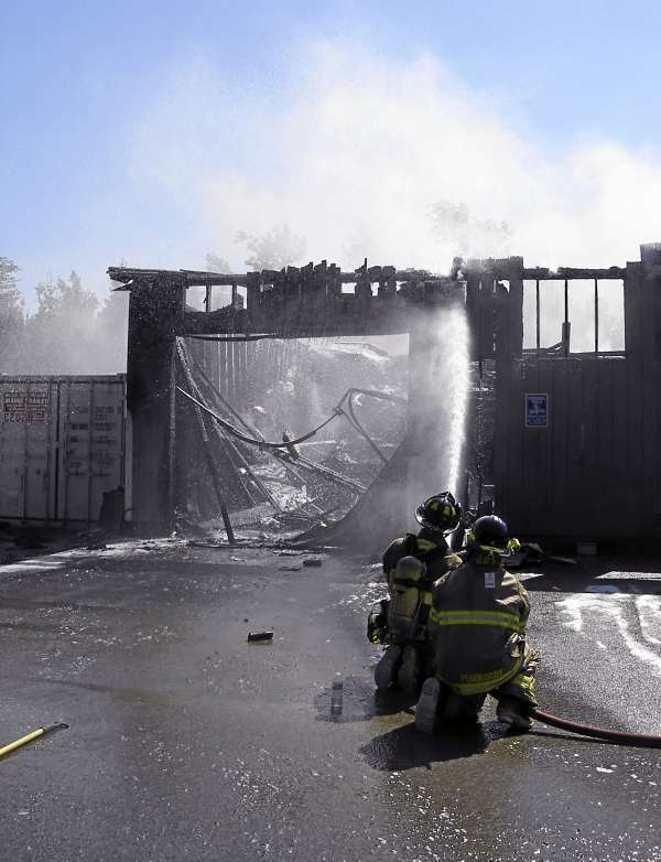 Firefighters hose down the remains of Newcomb's  Auto Body shop on Route 1 on Verona Island Monday afternoon. The fire apparently was started when sparks from a welder set a vehicle on fire. The blaze then spread to the building.  Bangor Daily News Photo by Rich Hewitt