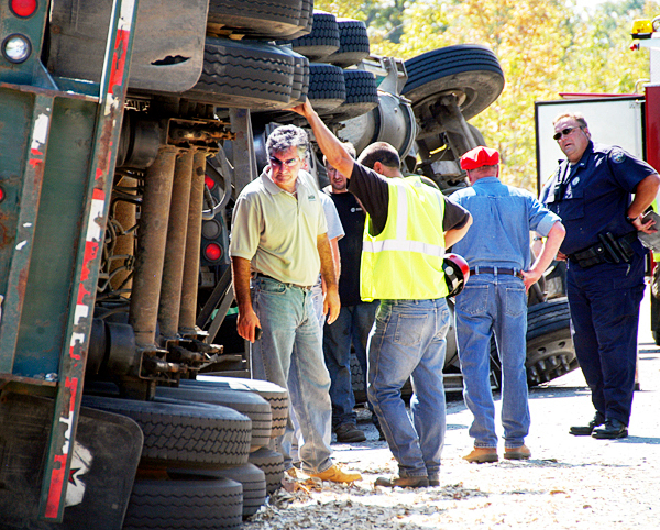 Gardner & Sons, Inc., co-owner Tom Gardner looks at the wheel assembly of one of his company?s trucks on Interstate 95 in Township 2, Range 9 on Monday. The truck?s driver was killed and the truck wrecked in the southbound lane. BANGOR DAILY NEWS PHOTO BY NICK SAMBIDES JR.
