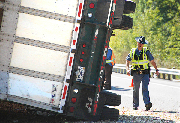 State Police Trooper Larry Anderson walks away from the wreckage of an 18-wheel truck on Interstate 95 in Township 2, Range 9 on Monday. A truck driver from Gardner & Sons, Inc., a logging company in Lincoln, died while attempting to drive a load of wood chips. The state police investigation continues. BANGOR DAILY NEWS PHOTO BY NICK SAMBIDES JR.