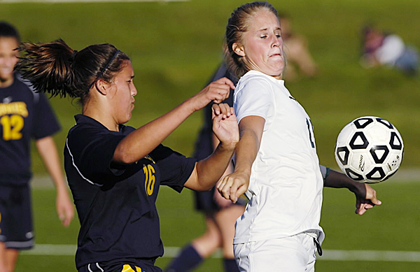 Husson University striker Megan Lajoie fights her way past the University of Southern Maine's Nikole Robbins (16) while controlling the ball during Tuesday's college soccer game at Boucher Field in Bangor. Husson won 6-1.  (BANGOR DAILY NEWS PHOTO BY JOHN CLARKE RUSS)