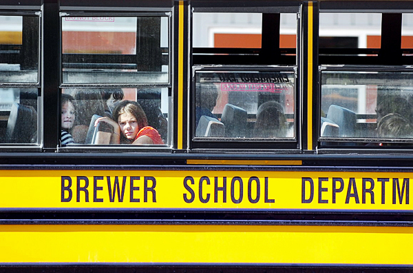 Despite the late summer heat wave, some area schools including Brewer were back in session Monday, Aug. 30, 2010. Students here gaze out windows as the buses at Brewer High School prepare to leave at the end of the first day of school, which saw temperatures in the low 90s. (Bangor Daily News/Bridget Brown)
