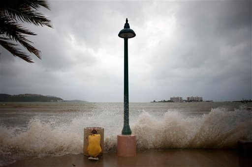 A boy takes cover from a wave caused by the approaching of the Hurricane Earl in Fajardo, Puerto Rico, Monday, Aug. 30, 2010. Earl battered some islands across the northeastern Caribbean with heavy rain and roof-ripping winds Monday, rapidly intensifying into a major storm on a path projected to menace the United States. (AP Photo/Ricardo Arduengo)