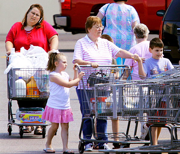 In this Aug. 26, 2010 photo, shoppers exit a Wal-Mart super center in Springfield, Ill. Americans are being more cautious about spending as economic conditions worsen. (AP Photo/Seth Perlman)