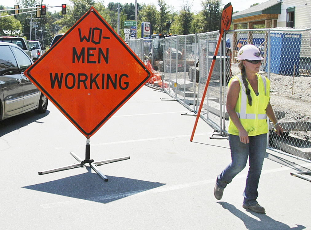 Construction worker Dawn Grover of Orrington walks by the sign she altered slightly at the $3.5 million Lakeview Senior Housing project on Main Street in Lincoln on Monday. Grover said she felt it important to let people know that she and Karen Harriman, a laborer, carpenter?s helper and forklift operator for Perry & Morrill, Inc., work on the job, too.       BDN PHOTOS BY NICK SAMBIDES JR.