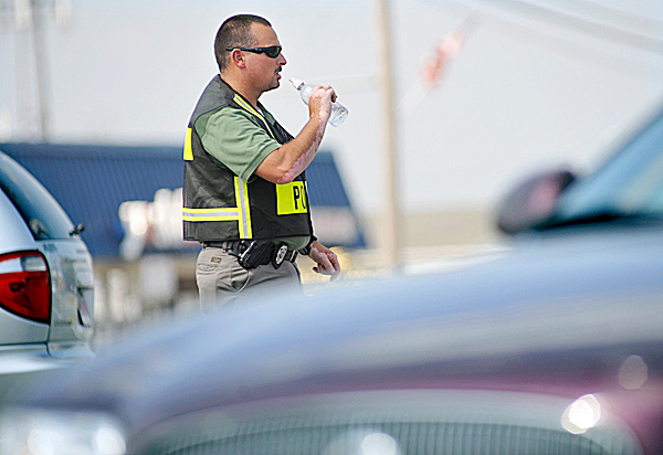 In Tuesday afternoon's heat Detective Corporal Paul Gauvin of the Brewer Police Dept. stayed hydrated with his bottled water while directing traffic after the traffic lights went dark on Wilson and State Streets during a power outage. 1500 customers in Brewer went without power for nearly an hour around noontime Tuesday. (Bangor Daily News/John Clarke Russ)