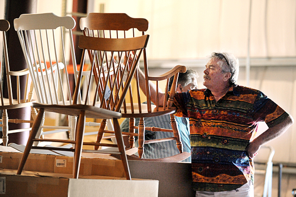 Paul Kelly of Hanover inspects wooden chairs maufactured at Moosehead Furniture in Moson on Tuesday, August 31, 2010 during the second auction of the furniture makers products and equipment. Kelly, the significant other of Louise Jonaitis, was on hand  to support  Jonaitis as she sucessfully bid on the entire plant for $1.1 million dollars. (Bangor Daily News/Kevin Bennett)