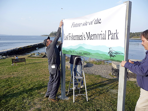 David Cline, left, helped erect a sign Tuesday evening that designates the location of the Lost Fishermen's Memorial Park in Lubec. Cline's son, Daryl, was lost a year ago when the fishing vessel he was working on sank in Cobscook Bay. Cline was the first person to approach the town about creating a memorial. The committee in charge has collected about $27,000 towards a goal of $200,000 for a statue and other items for the park. Buy Photo