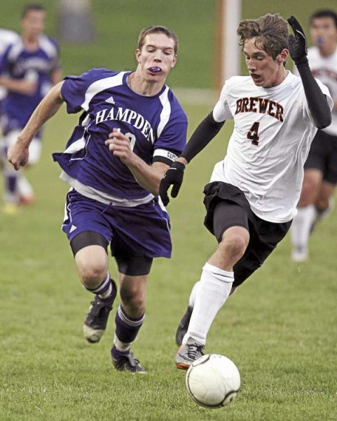 Tristan Wortman of Brewer (right) tries to elude Hampden Academy's Graham Safford during their Class A soccer game Tuesday, Sept. 21, 2010.