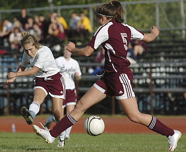 Ellsworth's Heather Holt blasts a shot at the goal as Caribou's Laura Collins defends against the attack on Thursday, September 23, 2010 at Ellsworth.