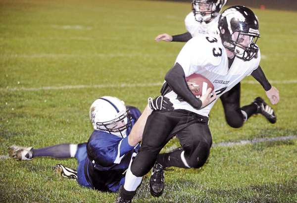 Calais-Woodland High School's Ryan Cavanaugh (right) breaks a tackle by Stearns High School's Cody Wallace as he scrambles for more yardage during the first quarter of the game in Millinocket Friday. (Bangor Daily News/Gabor Degre)