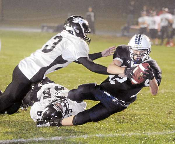 Billy Eurich (right) of Stearns escapes the tackle attempts of Ryan Cavanaugh (top left) and Jacob Sterner of Calais-Woodland and dives into the end zone for a touchdown in the third quarter of Friday night's football game in Millinocket. Stearns won 22-8. (BDN/Gabor Degre)