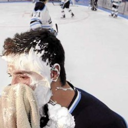 University of Maine freshman forward Carlos Amestoy wipes shaving cream from his face after Black Bear captain Tanner House shoved a towel of shaving cream into his face while he was doing a television interview on media day at Alfond Arena in Orono Thursday.
