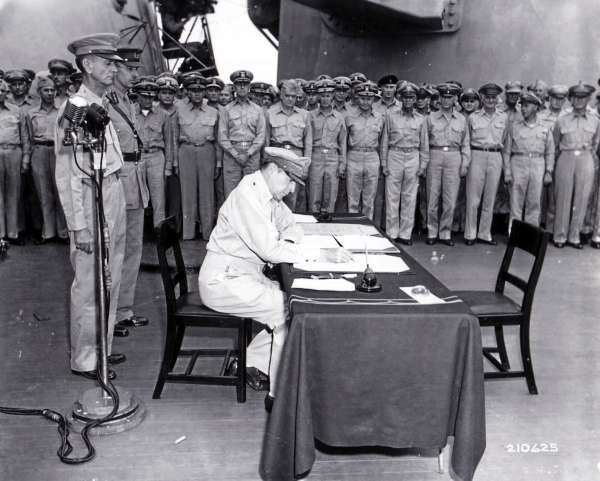 General MacArthur signs the Japanese surrender papers aboard the USS Missouri on September 2, 1945.  ASSOCIATED PRESS  [This photograph originally ran on page one of the Bangor Daily News on September 4, 1945.