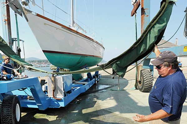 Gary Murphy (right) holds the travel lift strap while Shane Bradley maneuvers the trailer from under the lift as they haul out a Hinckley 42 sailboat at the Hinckley Co.'s boat yard in Southwest Harbor on Wednesday. Paul Frederick, the services manager at the company, said they will haul out about 50 boats before Friday afternoon in advance of the possible bad weather caused by Hurricane Earl. Teh storm is forecast to pass near the Maine coast, but it is uncertain how close. Many boat owners want their vessels out of the water just in case.  (BANGOR DAILY NEWS PHOTO BY GABOR DEGRE)