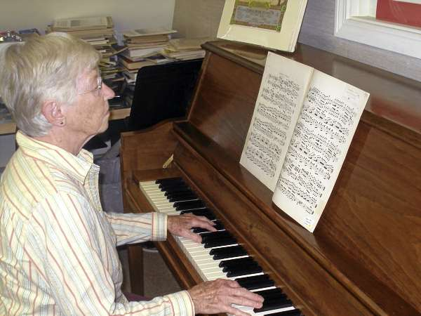 Win Pusey, a volunteer at teh Bagaduce Music Lending Library in Blue Hill, plays the Bangor March recently on the library's piano. The library has donated a copy of the piece, another copy of which was discovered in a gilded frame last month, to the Bangor Public Library. Bangor Daily News photo by Rich Hewitt