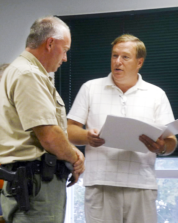 Maine Senator Kevin Raye (R-Eastport) reads a Legislative sentiment to Maine Marine Patrol Officer Russell Wright at the Lubec selectmen's meeting Thursday night. The sentiment, presented by Raye and State Rep. David Burns, recognized Wright, Joseph O'Brien and Gary Brown for their heroic actions when an arsonist set a mobile home on fire in Lubec in June. There were children and adults in the trailer, Selectman Bill Daye said, and the arsonist stole fuel from a town vehicle and set the mobile home on fire. The family was rescued and the arsonist arrested by Wright. In all, the selectmen recognized 14 people Thursday night as Hometown Heroes. BANGOR DAILY NEWS PHOTO BY SHARON KILEY MACK