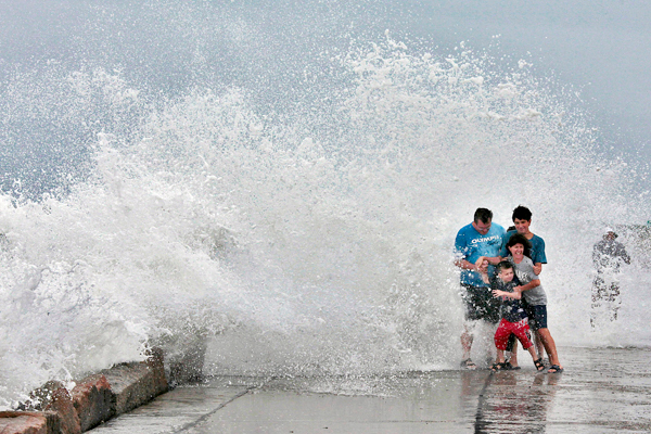 The Gallishaw family from Seekonk, Mass., braces for a large wave as it crashes over the Goosebury Island causeway in Westport, Mass., as Hurricane Earl approaches Friday.  AP PHOTO/  STANDARD TIMES/ PETER PEREIRA