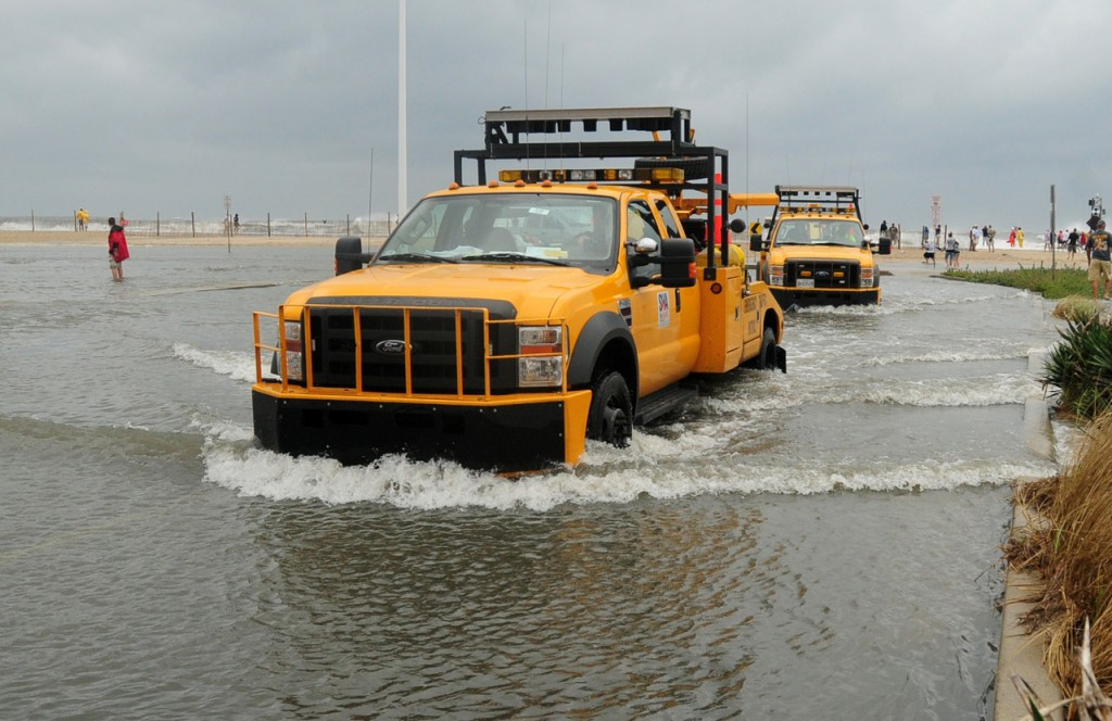 Crew from the Maryland State Highway Administration exit the inlet parking lot after high storm surge from Hurricane Earl covered the area in knee-deep water  in Ocean City, Md., on Friday, Sept. 3, 2010.  The water was closed to all swimmers due to the rough surf, and beach patrol struggled to keeping onlookers far back on the beach. (AP Photo/ The Salisbury Daily Times, Laura Emmons)