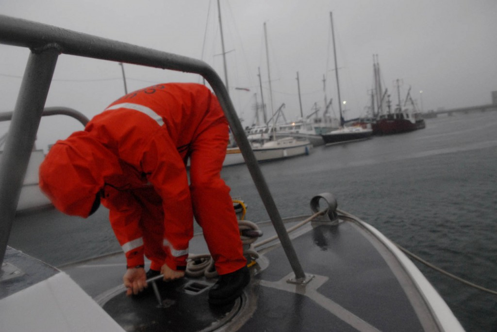 As Tropical Storm Earl's heavy winds and rains belted Eastport's breakwater early Saturday morning, Kevin Cummings of the U.S. Coast Guard Station Eastport secured the forepeak hatch after checking for any storm water in the bilge area of the station's 41-foot utility boat .(Bangor Daily News/John Clarke Russ)