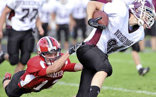 Nokomis' Dan Tucker is slowed by Camden Hills' Alex Crans in the first quarter of their game Saturday afternoon, September 5, 2010. Camden defeated Nokomis 60-28 at Don Palmer Field in Rockport. (Bangor Daily News/John Clarke Russ)