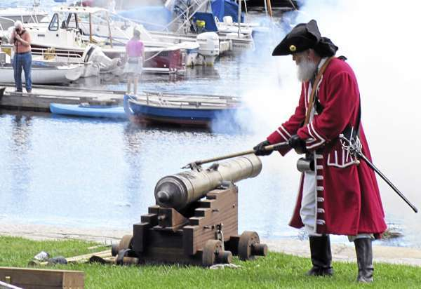 A British troop fires his cannon at a pirate ship in Camden Harbor in his attempt to defend the shore against pirates. The mock battle took place Sunday, Sept. 5, 2010 during the 16th annual Camden Windjammer Festival. (Bangor Daily News/Christopher Cousins)