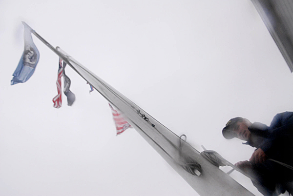 As Tropical Storm Earl's heavy winds and rains belted downtown Eastport early Saturday morning, U.S.C.G. Seaman Benjamin Jacobson of Calais checked the flag lines in front the U.S. Coast Guard Station Eastport.(Bangor Daily News/John Clarke Russ)