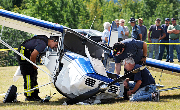 Levant fire department personnel, Lt. Steve Burgess, left, Capt. Joey Carrow, center, and firefighter Skip McIntosh inspect the wreckage of a Cessna 140 tail dragger that crashed on Monday, September 6, 2010 on a grass airstrip off the Pember Road in Levant.  BANGOR DAILY NEWS PHOTO BY KEVIN BENNETT