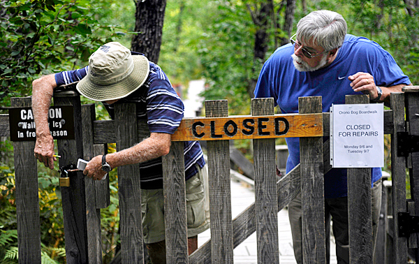 Orono Bog Boardwalk maintenance supervisor Phil Locke (cq), left, of Bangor and boardwalk volunteer Jerry Ledwith of Bangor look over a broken latch to the front gate of the boardwalk after learning Monday morning that various sections the boardwalk were vandalized sometime after it closed for the evening Sunday.  BANGOR DAILY NEWS PHOTO BY JOHN CLARKE RUSS