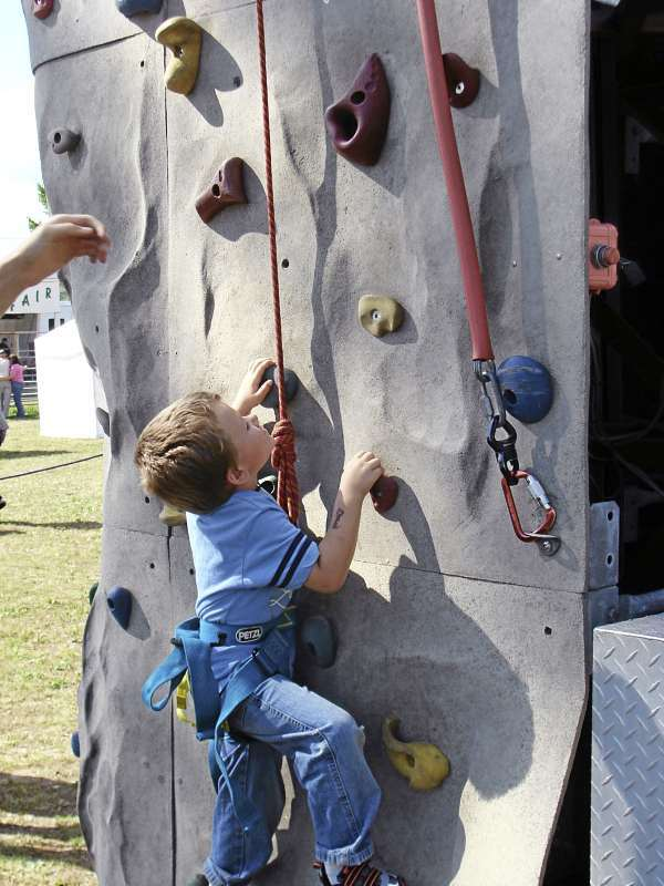 Dominic Martin, 4, of Garland, tried the Adventure Climbing wall at the  Harmony Free Fair Saturday, but he become a little scared when his feet  left the ground. (Bangor Daily News Photo by Diana Bowley)