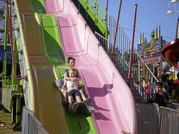 Liam Siggins, 6, of Medford, Ma. hangs on to his little sister, Ayla, 4, as they fly over a bump on the monster slide ride at the Blue Hill Fair Monday. The youngsters were visiting the last day of the fair with their parents, Suzanne and Arthur Siggins.   (Bangor Daily News Photo by Rich Hewitt)