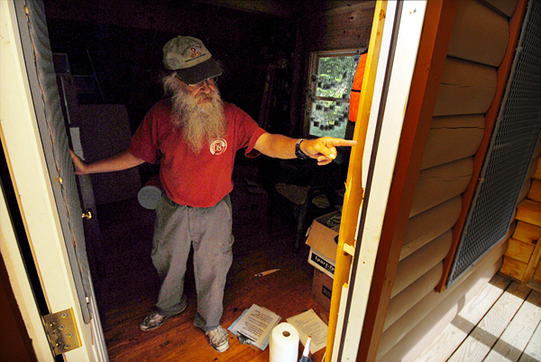 Left to right: Orono Bog Boardwalk director Jim Bird shows the vandalized door frame of the boardwalk's maintenance cabin Monday morning. Bird learned Monday morning that the cabin and various sections the boardwalk were vandalized sometime after it closed for the evening Sunday.  BANGOR DAILY NEWS PHOTO BY JOHN CLARKE RUSS