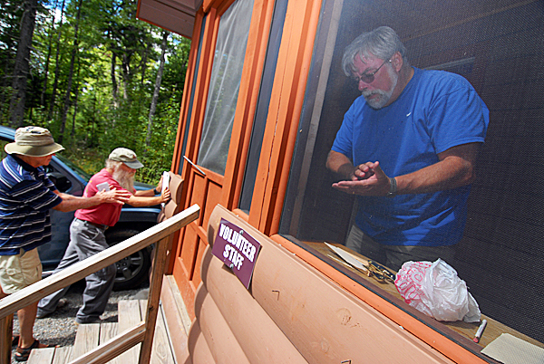 Left to right: Orono Bog Boardwalk maintenance supervisor Phil Locke of boardwalk director Jim Bird and volunteer Jerry Ledwith repair the boardwalk maintenance cabin Monday morning. It sustained signage and doorway damage. They learned Monday morning that the cabin and various sections the boardwalk were vandalized sometime after it closed for the evening Sunday. (Bangor Daily News/John Clarke Russ)