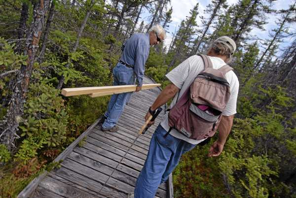 Orono Bog Boardwalk director Jim Bird, right, and volunteer Tom Hanson of Orrington deliver lumber and tools on Tuesday to various sites along the Orono Bog Boardwalk that were damaged by vandals early Monday morning. (Bangor Daily News/John Clarke Russ)