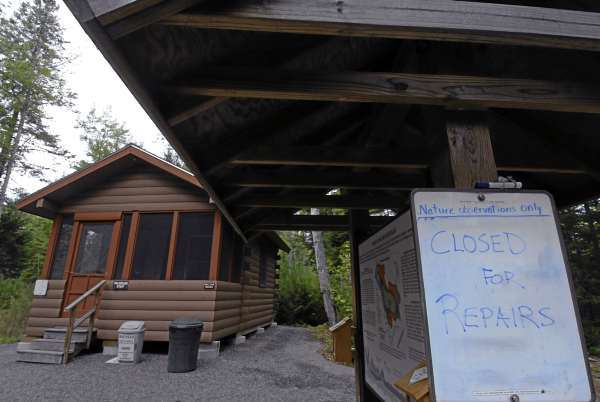 A dry erase board announces the Orono Bog Boardwalk's closure as boardwalk staff and volunteers were busy Tuesday repairing Monday's vandalism. The cabin sustained signage and doorway damage. (Bangor Daily News/John Clarke Russ)