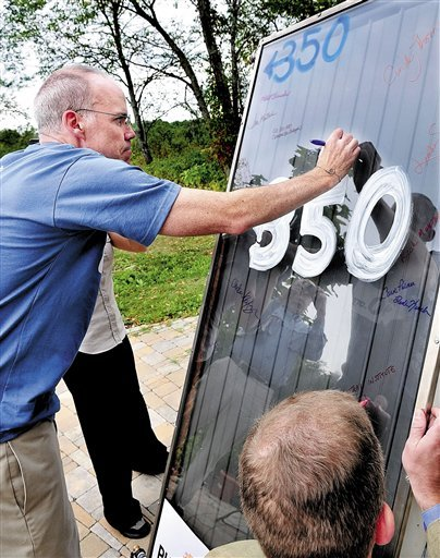 Environmental activist and author Bill McKibben and others sign a solar panel during a news conference at Unity College in Unity, Maine, on Tuesday, Sept. 7, 2010. McKibben and students will take the panel that once stood atop the White House in Washington, back to Washington in hopes of having President Barack Obama reinstall it in an effort to promote solar energy. (AP Photo/Morning Sentinel, David Leaming)