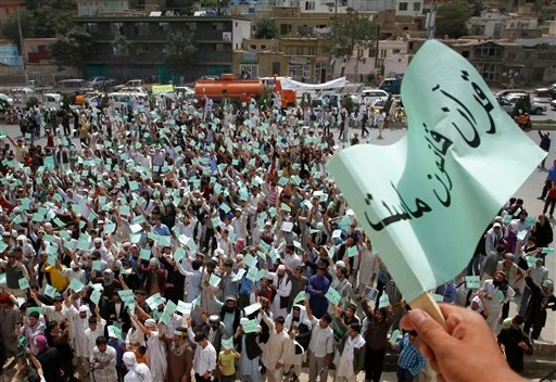 Afghans move banners saying &quotQuran is our law, Islam is our religion&quot during a demonstration against the United States, in Kabul, Afghanistan, Monday, Sept. 6, 2010. Hundreds of Afghans railed against the U.S. and called for President Barack Obama's death at a rally in the capital Monday to denounce the American church's plans to burn the Islamic holy book on 9/11. (AP Photo/Musadeq Sadeq)