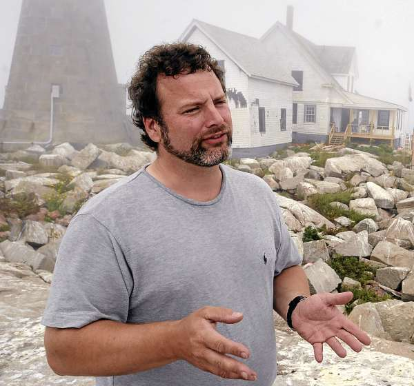 Sean Todd teaches biology and marine science at the College of the Atlantic.  He is one of the people who leads the research on Mount Desert Rock that is home to the college's whale research station (background). (Bangor Daily News/Gabor Degre)