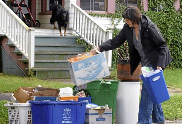 &quotI'm excited about it,&quot said Brewer resident Gail Ferland of the city's single sort recycling program as she took recyclables to the curb on School Street on Thursday, Sept. 9, 2010.  The single sort method allows users to put all their recyclables into one bin or can for pickup. (Bangor Daily News/Scott Haskell)