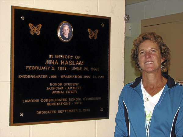 Patti Haslam of Lamoine stands Friday next to a memorial plaque for her daughter, Janina &quotJina&quot Haslam, in the gym of Lamoine Consolidated School. The renovated gym was dedicated last week in memory of her daughter, who biking on a local road five years ago when she was struck and killed by a car. BANGOR DAILY NEWS PHOTO BY BILL TROTTER