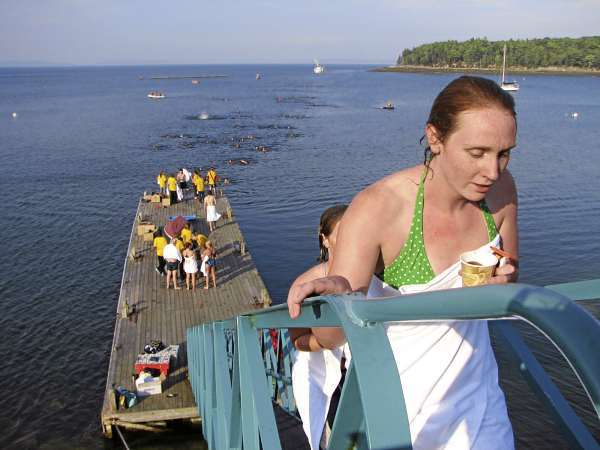 College of the Atlantic student Amelia Eshleman walks up the ramp from the COA pier Wednesday after completing the school's annual swim from Bar Island, seen in the background, to the COA campus. Eshleman is one of 360 students at the Bar Harbor school, the highest enrollment ever in COA's 38-year history. BANGOR DAILY NEWS PHOTO BY BILL TROTTER