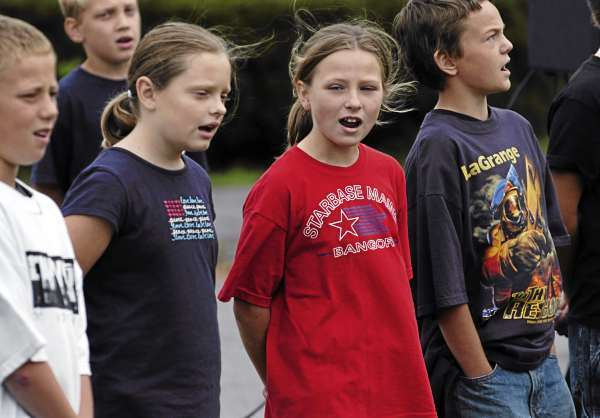 Grade 4/5 students (left to right) Eddy Pierce, Emma Nutting, Kylie Trafton and Melvin Ames sing &quotGod Bless the USA&quot during a September 11 memorial service on the lawn at the Marion C. Cook School in LaGrange on Friday, September 10, 2010. (Bangor Daily News/Kevin Bennett)